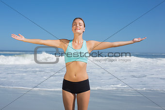 Fit woman standing on the beach with arms out