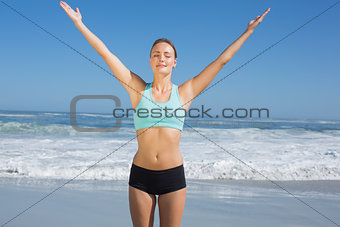 Fit woman standing on the beach with arms up