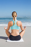 Fit woman sitting on the beach in lotus pose