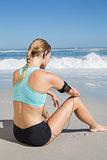 Fit woman sitting on the beach taking a break