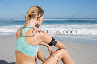 Fit woman sitting on the beach taking a break