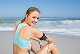 Fit woman sitting on the beach taking a break smiling at camera