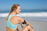 Fit woman sitting on the beach taking a break smiling