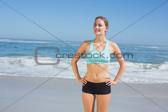 Fit woman standing on the beach with hands on hips