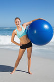 Fit woman standing on the beach holding exercise ball