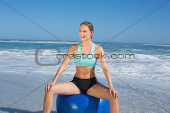 Fit woman sitting on exercise ball at the beach