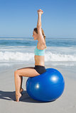Fit woman sitting on exercise ball at the beach stretching arms