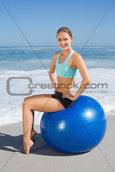 Fit woman sitting on exercise ball at the beach smiling at camera