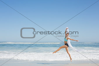 Fit woman jumping gracefully on the beach with scarf