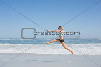 Fit woman jumping gracefully on the beach