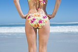 Lower rear view of fit woman in floral bikini at beach