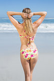 Blonde fit woman in floral bikini at beach