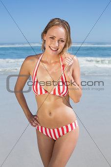 Blonde fit woman in striped bikini at beach smiling at camera