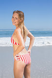 Smiling fit woman in striped bikini at beach