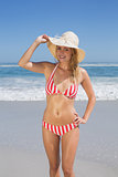 Gorgeous fit woman in striped bikini and sunhat at beach