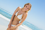 Beautiful blonde in white bikini smiling at camera on the beach
