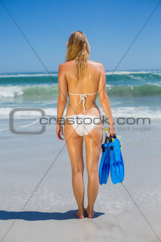 Fit woman in white bikini holding snorkeling gear on the beach