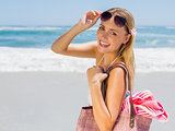 Smiling blonde carrying bag and towel on the beach