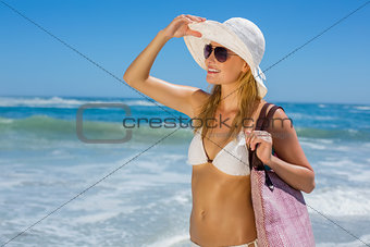 Smiling blonde in white bikini carrying bag on the beach