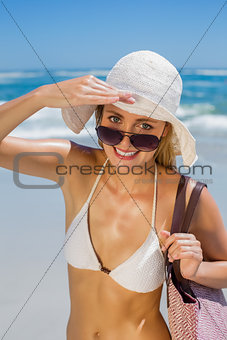 Smiling blonde in white bikini carrying bag on the beach