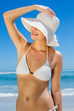 Smiling blonde in white bikini and sunhat on the beach