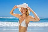 Smiling blonde in white bikini and sunhat on the beach