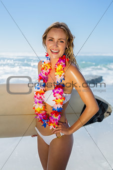 Smiling blonde surfer in white bikini and garland on the beach