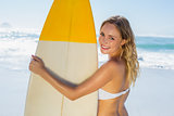 Smiling blonde surfer in white bikini holding her board on the beach