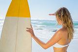 Blonde surfer in white bikini holding her board on the beach