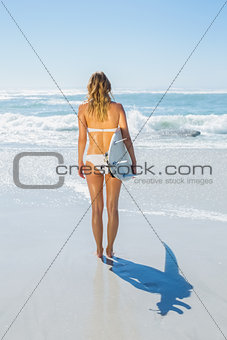 Blonde surfer in white bikini holding her board on the beach