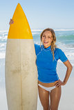 Blonde happy surfer holding her board on the beach