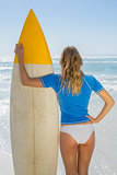 Blonde surfer holding her board on the beach