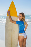 Blonde smiling surfer holding her board on the beach