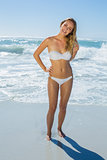 Gorgeous blonde in white bikini standing in the sea
