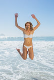Gorgeous blonde in white bikini jumping by the sea