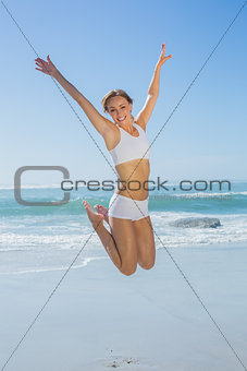Gorgeous fit blonde jumping by the sea with arms out