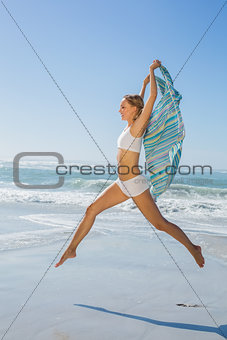 Gorgeous fit blonde leaping by the sea with scarf