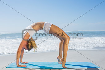 Gorgeous fit blonde in crab pose on the beach