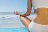 Fit woman sitting in lotus pose on the beach