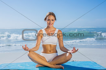 Fit smiling woman sitting in lotus pose on the beach