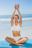 Fit calm woman sitting in lotus pose on the beach