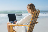 Gorgeous blonde sitting on deck chair using laptop on beach
