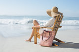 Woman sitting on wooden deck chair by the sea