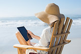 Smiling blonde sitting on wooden deck chair by the sea using tablet