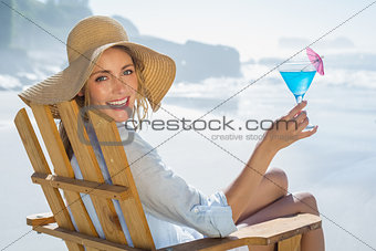 Smiling blonde relaxing in deck chair by the sea holding cocktail