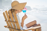 Smiling blonde relaxing in deck chair by the sea sipping cocktail