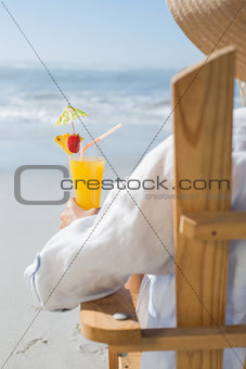 Woman relaxing in deck chair by the sea holding cocktail