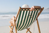 Woman relaxing in deck chair by the sea
