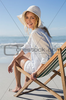 Smiling blonde relaxing in deck chair by the sea
