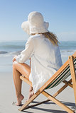 Blonde relaxing in deck chair by the sea